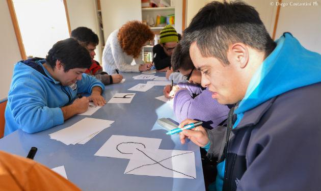 Jovenes de Puentes de Luz dibujando los numeros para las pecheras del tetratlon de Chapelco 2016 DAC_3565